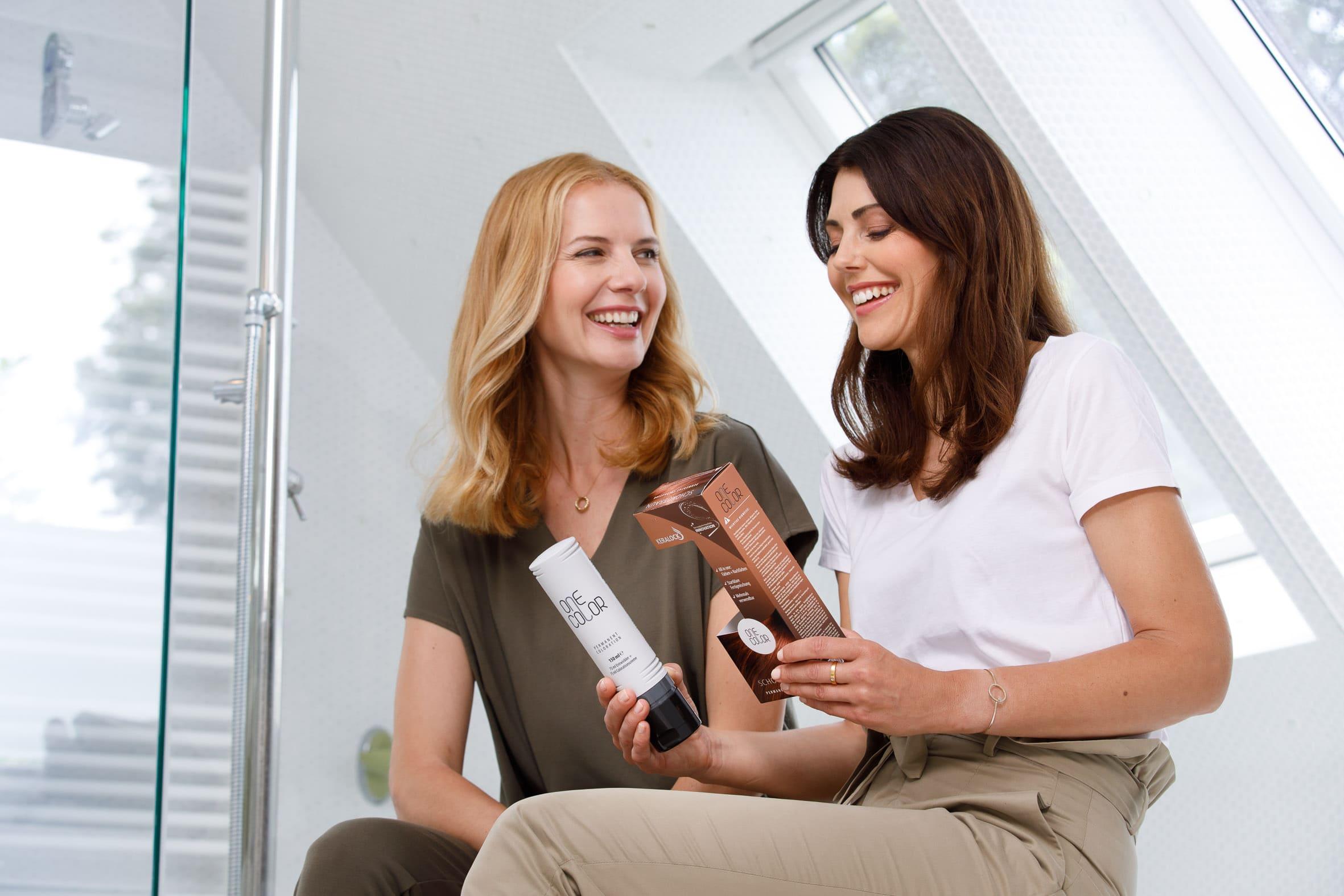Zwei Frauen betrachten ONE COLOR Flasche und Packung